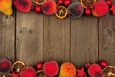 Christmas fruit decoration double border over a dark rustic wood background