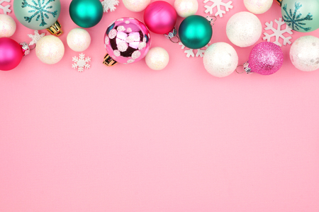 Modern pastel Christmas bauble top border over a light pink background