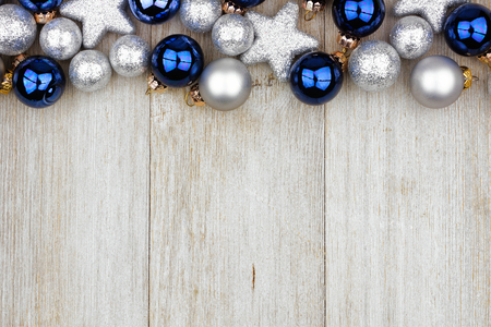 Christmas top border of blue and silver ornaments on a rustic light gray wood background Stock Photo