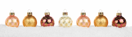 Christmas border of copper and gold ornaments in snow isolated on a white background