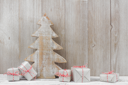 Shabby chic wooden Christmas tree with gift boxes against a rustic light gray wood background
