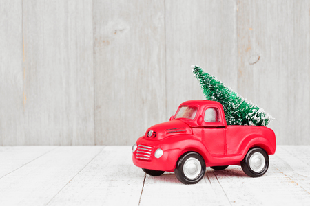 Red toy truck with Christmas tree, in snow against a bright wooden background