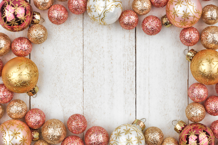 Christmas frame of rose gold and golden ornaments on a rustic white wood background