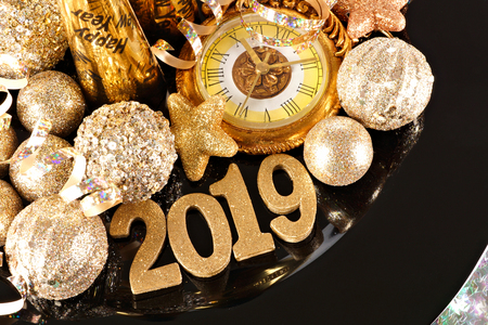 Shiny 2019 numbers with New Years themed gold decor, party materials and clock on a black charger Stock Photo