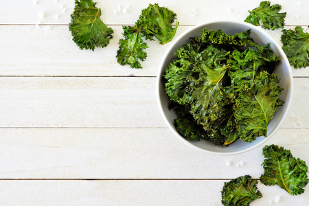 Healthy kale chips in a bowl. Above scene, corner border on a white wood
