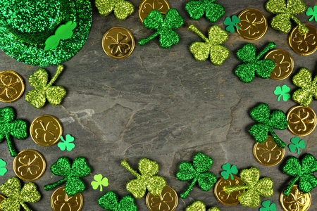 St Patricks Day frame with shamrocks, gold coins and leprechaun hat over a dark slate