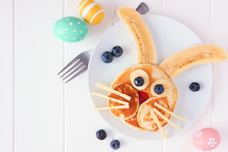 Fun Easter Bunny pancakes on a white plate. Close up table scene against a white wood background.