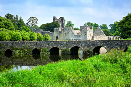 Medieval Desmond Castle, Ireland with old stone bridge, Adare, County Limerick