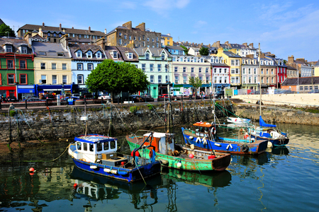 Old boats with colorful harbor buildings in the port town of Cobh, County Cork, Ireland