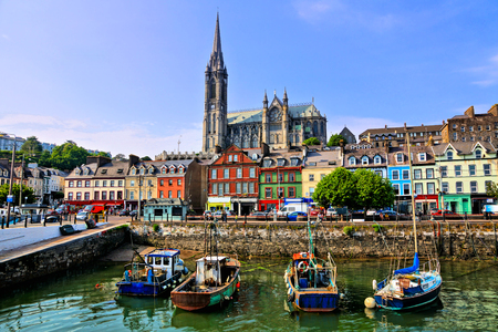 Colorful buildings and old boats with cathedral in the harbor of Cobh, County Cork, Ireland