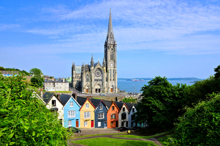 Colorful row houses with towering cathedral in the port town of Cobh, County Cork, Ireland