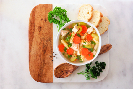Chicken noodle soup with vegetables, top view on a marble and wood serving platter