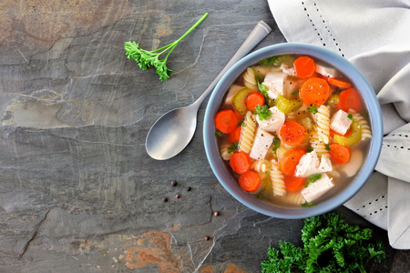 Homemade chicken noodle soup with vegetables. Above scene on a dark slate background. Banque d'images