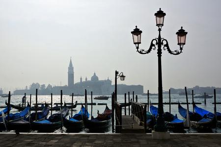 Gondolas at St Marks square with misty San Giorgio di Maggiore church silhouette behind, Venice, Italy