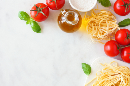 Pasta ingredients including fresh linguine, tomatoes, olive oil and basil, above view, corner border against a white marble background with copy space Stockfoto