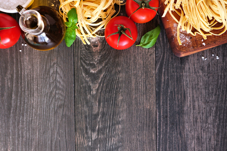 Pasta ingredients including fresh linguine, tomatoes, olive oil and basil, above view, top border against a wooden background with copy space