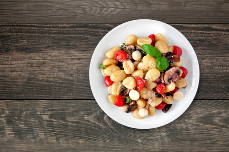 Gnocchi with tomatoes, mozzarella, mushrooms and basil, top view over a dark wood background Foto de archivo