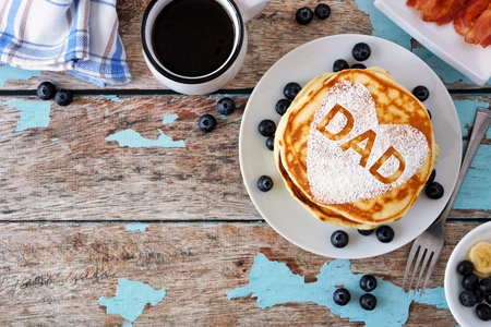 Fathers Day pancake breakfast with heart shape and DAD letters, above view corner border on rustic blue wood