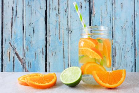 Agua de desintoxicación con infusión de naranja y lima en un vaso de tarro de albañil.