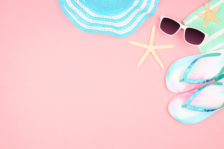 Summer vacation beach accessories corner border on a pastel pink background with copy space