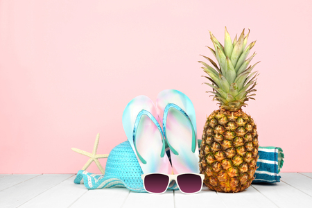 Summer vacation beach accessories against a pastel pink background