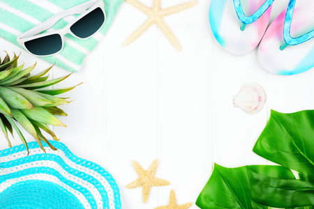 Frame of summer vacation beach accessories on a white wood background with copy space