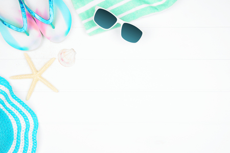 Corner border of summer vacation beach accessories on a white wood background with copy space