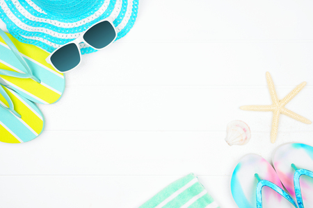 Beach accessories on a white wood background. Summer vacation concept border with copy space. Sunglasses, sea shells, towel, flip flops, and blue striped hat. Stock Photo