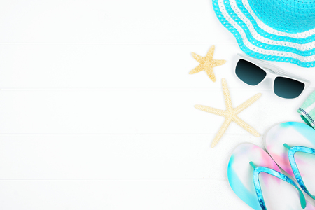 Side border of summer vacation beach accessories on a white wood background with copy space