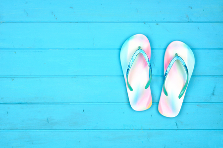 Summer flip flops on a blue wood background, top view with copy space