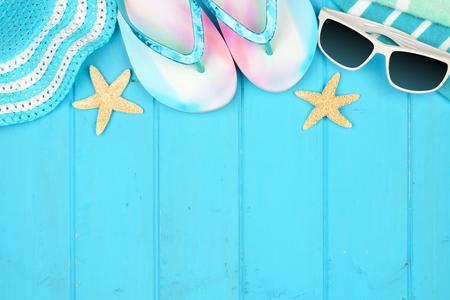 Bordo superiore degli accessori da spiaggia per le vacanze estive su uno sfondo di legno blu con spazio per le copie