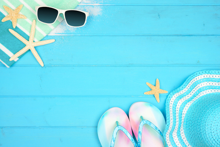 Summer vacation beach accessories border on a blue wood background with copy space Stock Photo