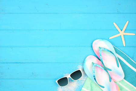 Summer vacation beach accessories corner border on a blue wood background with copy space Stock Photo