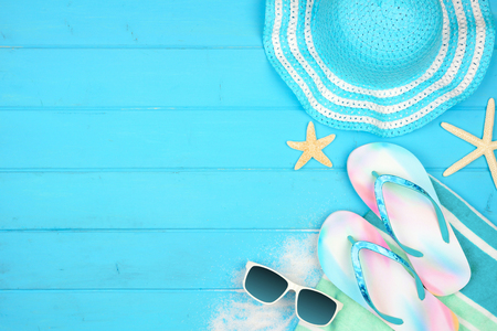 Summer vacation beach accessories side border on a blue wood background with copy space Stock Photo