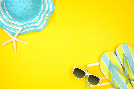 Summer vacation beach accessories border on a yellow background with copy space
