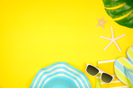 Summer vacation beach accessories corner border on a yellow background with copy space Banco de Imagens - 124939629