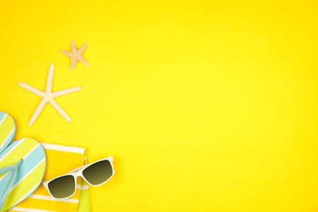 Summer vacation beach accessories side border on a yellow background with copy space