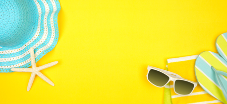 Summer vacation beach accessories banner on a yellow background with copy space
