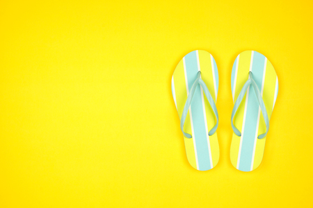 Summer flip flops on a yellow background, top view with copy space Banco de Imagens - 124939636