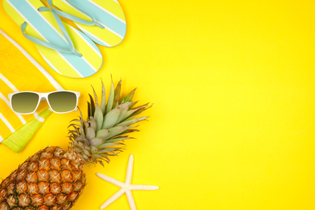 Beach accessories on a yellow background. Summer vacation concept side border with copy space. Sunglasses, starfish, towel, flip flops and pineapple. Banco de Imagens