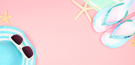 Summer vacation beach accessories banner on a pastel pink background with copy space