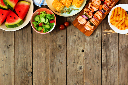 Summer BBQ or picnic food top border, top view over a wood background