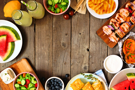 Summer BBQ or picnic food frame, top view over a wood background