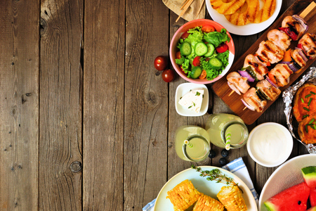 Summer BBQ or picnic food side border, top view over a wood background