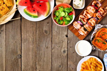 Summer BBQ or picnic food corner border, top view over a wood background