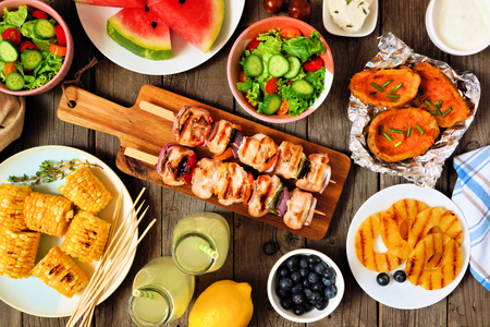 Summer BBQ or picnic food above view table scene over wood