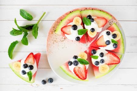 Summer watermelon pizza with blueberries, strawberries, bananas and yogurt, above view over white wood