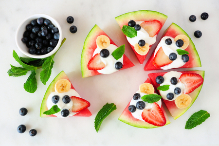 Summer watermelon pizza with blueberries, strawberries, bananas and yogurt, top view over marble