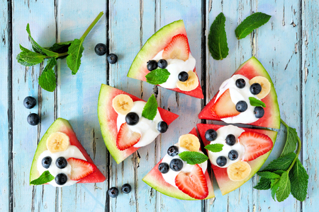 Healthy watermelon pizza with blueberries, strawberries, bananas and yogurt, top view over blue wood