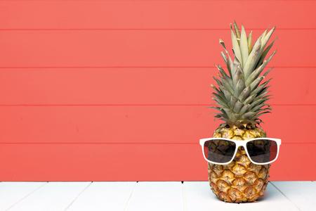 Ananas hipster con occhiali da sole su uno sfondo di legno color corallo vivente